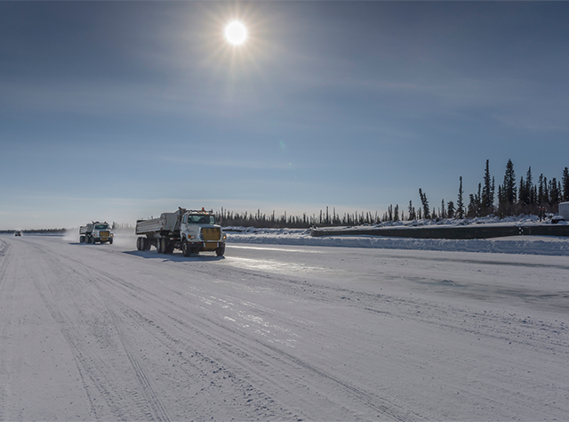 Construction trucks driving on a road in northern Canada